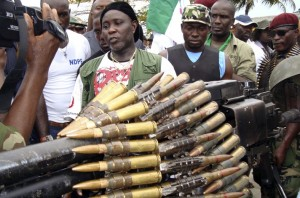 Nigerian militant commander Tom addresses the media as arms surrendered by former Nigerian militants are displayed at an arms collection centre in the oil hub Port Harcourt